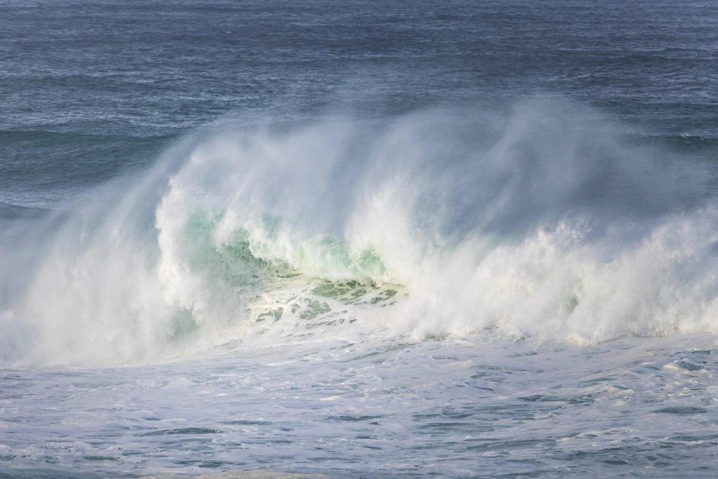 large white wave crashing on a dark blue ocean with green highlights